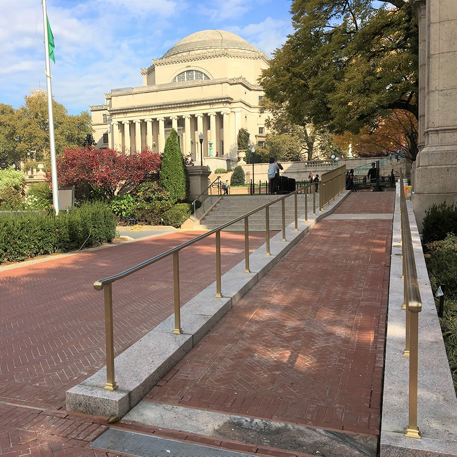 A masonry accessibility ramp leads to College Walk with a view of the Low Memorial Library in the background.