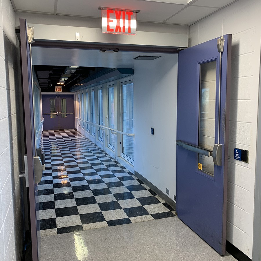 In the Pupin Hall building, a button on the wall of a checkered-floor hallway open sky bridge doors.