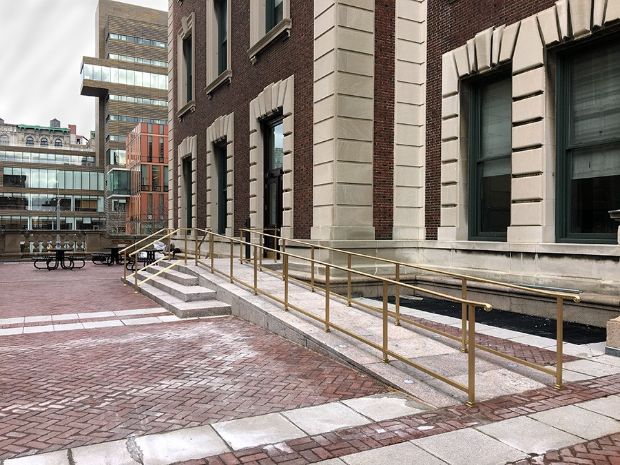 A masonry ramp with bronze handrails leads up to the entrance of the brick-building, Havermeyer.