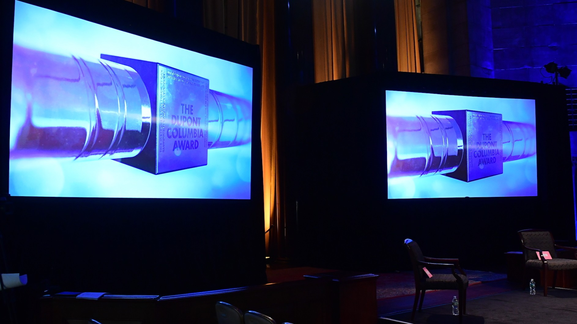 Two big screens with identical images of a silver baton with duPont Columbia Award written on them