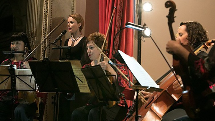The Cassat String Quartet sit with their instruments in front of their music stands on stage with a red curtain to their left and Magdalena Baczewska at a microphone.