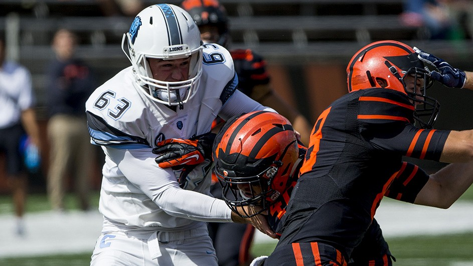 Patricky Eby, number 63, on the Columbia football team stopping an opponent.