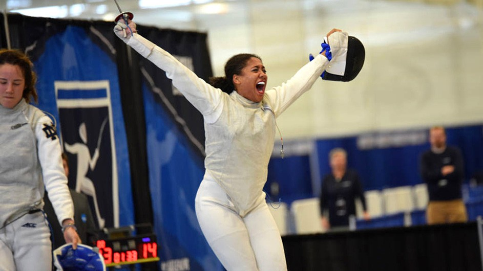 Iman Blow still in uniform and with a sword in hand, celebrates a fencing victory.