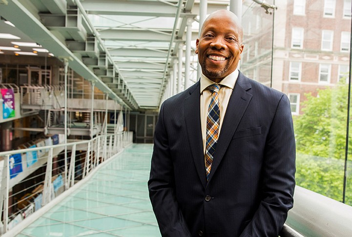 Lance Freeman in a dark gray suit smiling, standing on a glass ramp that looks over a tree on the right and other floors on the left.