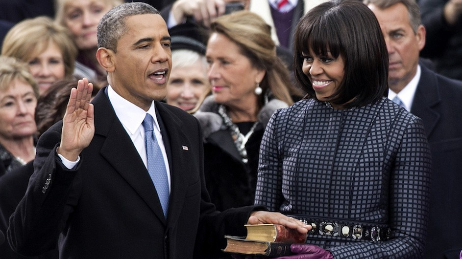 President Barack Obama raises his right hand and he and First Lady Michelle Obama place a hand on a bible.