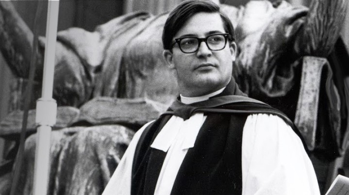 A black and white photo of Chaplain John Dyson Cannon in commencement vestments with an academic hood, standing in front of the Alma Mater statue.