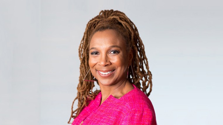 Kimberle Crenshaw in a pink blazer in front of a gray background