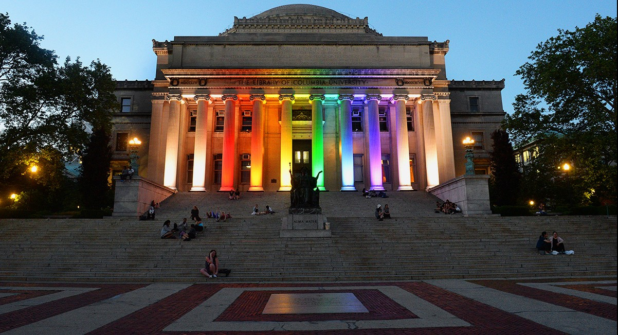 Low Library's Romanesque columns lit up in rainbow colors.