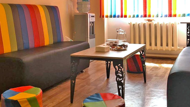 A rainbow-themed therapy room with a sofa, tufts, coffee table, a water cooler, and rainbow curtains.