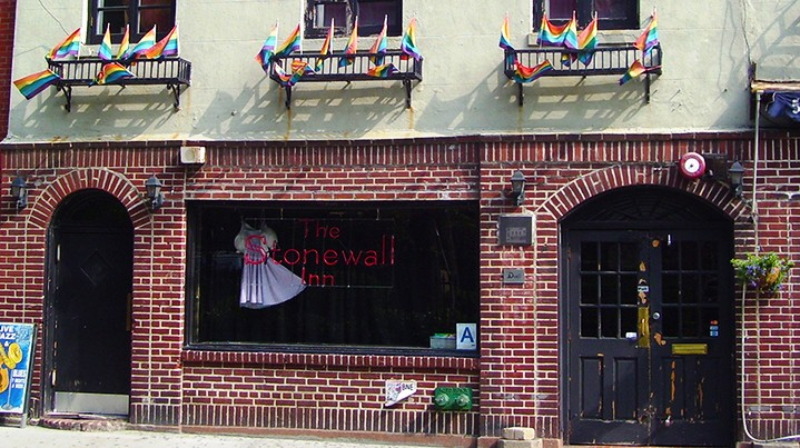 The red brick storefront of The Stonewall Inn with three windows above lined with rainbow flags.