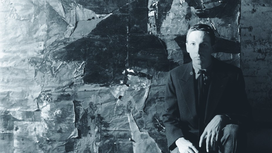 The artist Robert Rauschenberg, a man with close-cropped hair, is seated in front of one of his artworks