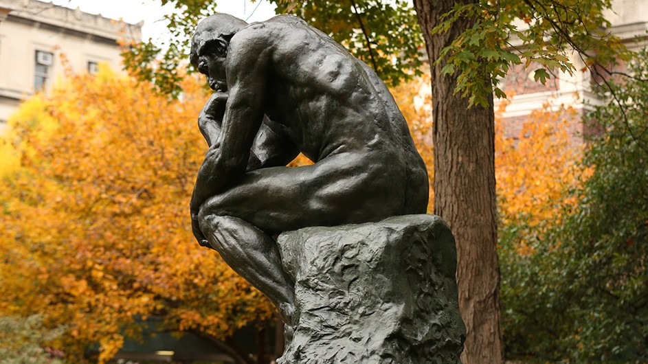 A statue of a thinking man in front of trees with fall foliage.