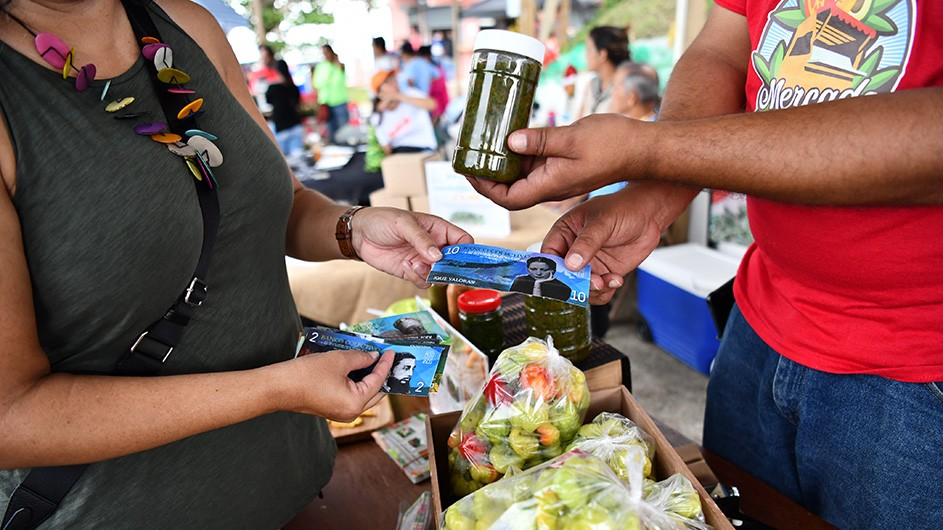 A customer exchanges art-crafted currency for spices from a food vendor in an outdoor market on Puerto Rico.