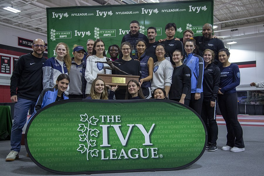 22 fencing athletes and coaches pose with a championship trophy against a green Ivy League athletics backdrop in a fencing room.