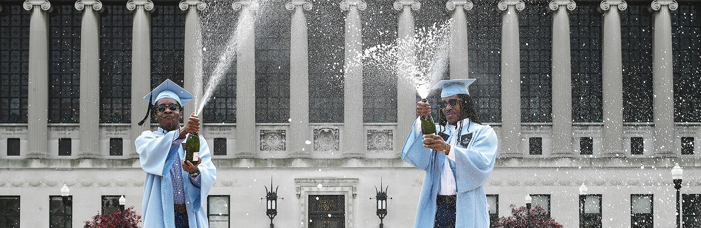 Two Columbia graduates in blue caps and gowns pop champagne in front of Butler Library.