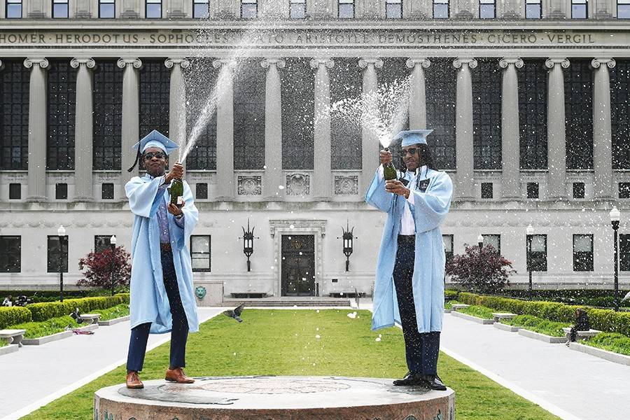 Two Columbia graduates in graduation caps and gowns pop champagne in front of Butler Library.