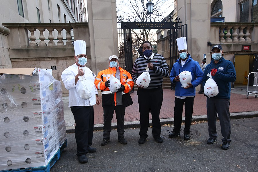 Five people stand in front of Columbia University's gates holding turkeys to give away.