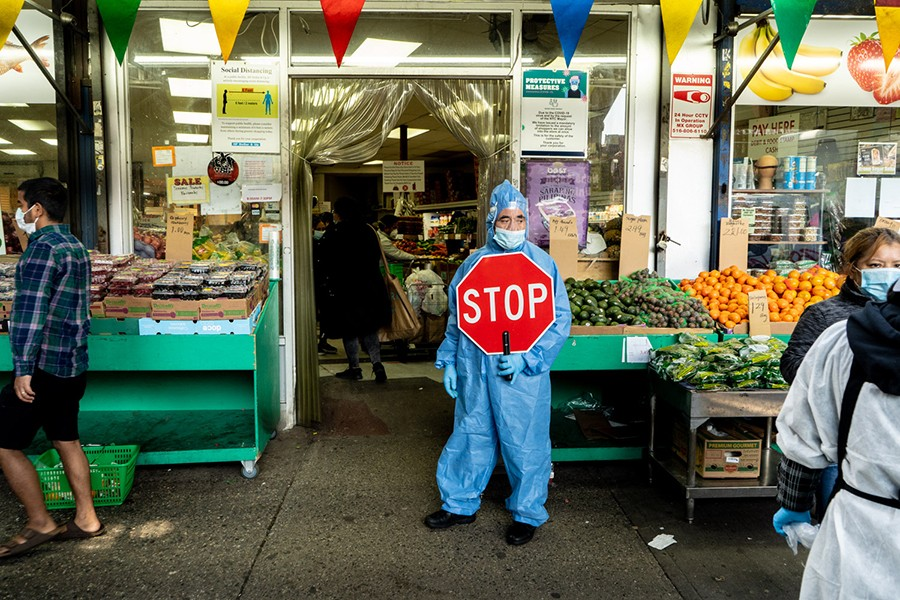 A person in full-body Personal Protective Equipment, mask, and face shield stands with a stop sign at an entrance to a New York City bodega.