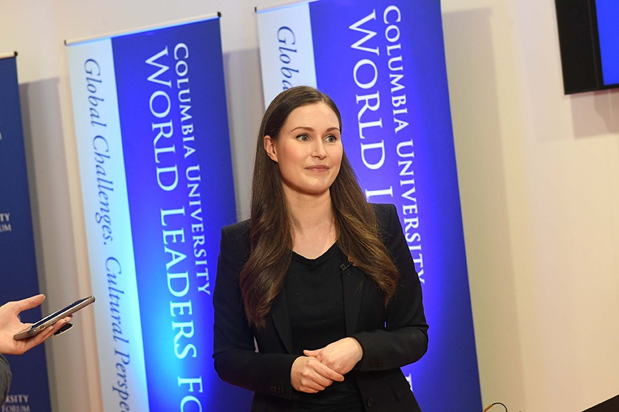 "Sanna Marin, Prime Minister of Finland, poses against blue banners reading ""Columbia University World Leaders Forum."""