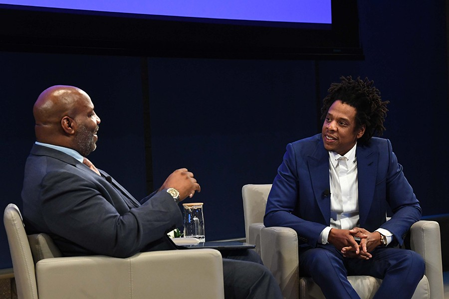 "Professor Jelani Cobb and Shawn ""JAY-Z"" Carter sit in tan chairs in front of a black backdrop in an auditorium at The Forum."