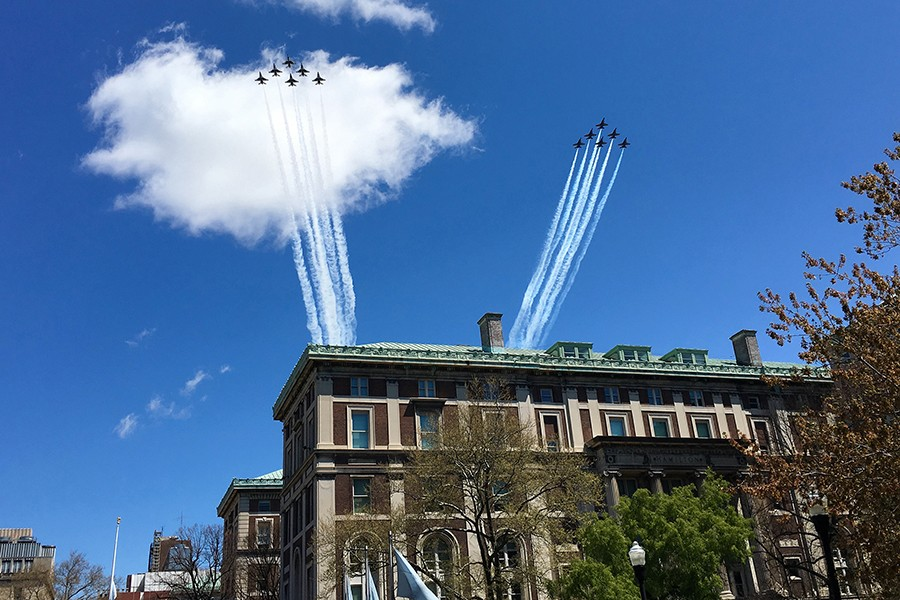 Two teams of six Thunderbird and Blue Angels jet planes fly across a blue sky with clouds over Columbia University's Morningside campus buildings.