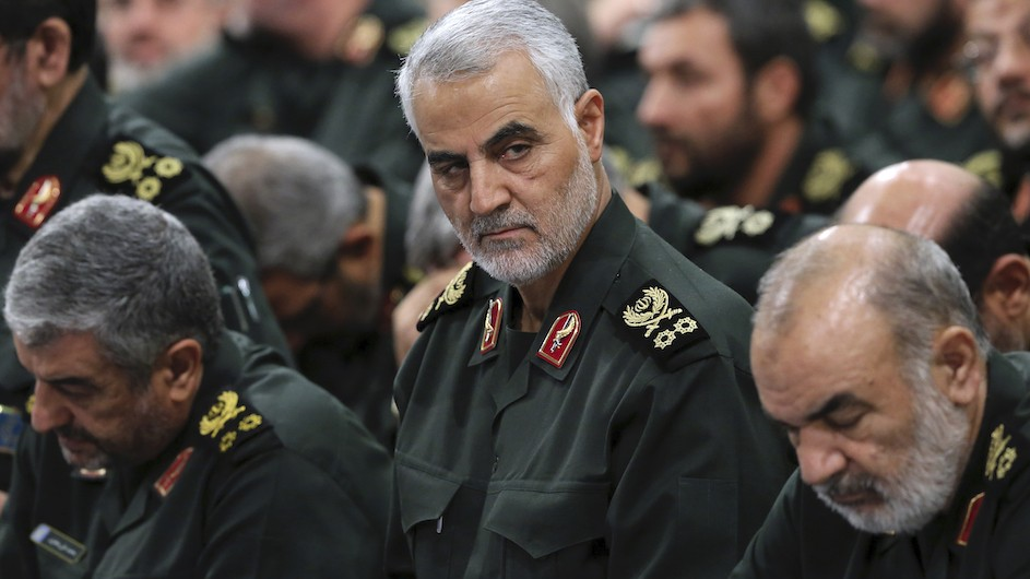 Iranian General Qasem Soleimani with gray hair and dressed in green military uniform surrounded by other Iranian officers in similar uniforms.