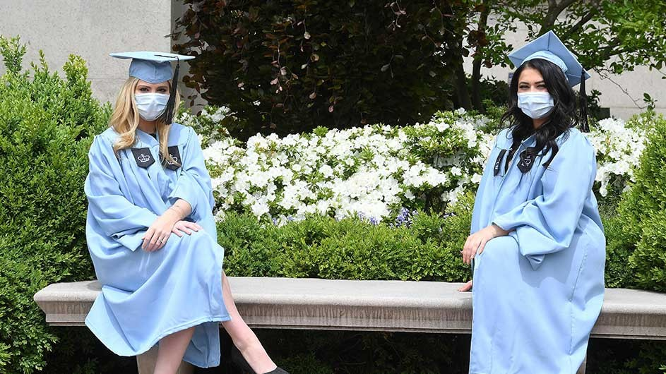 Two women in Columbia blue caps and gowns and face masks sit on a bench on campus.