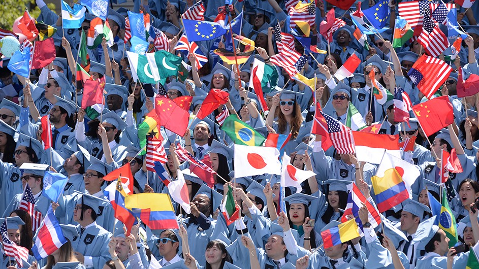 A crowd of students waive international flags at Columbia's annual Commencement