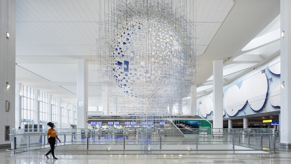 A circular sculpture hangs from the ceiling in an airport hall.