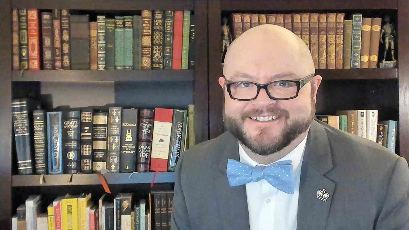 Allen Darrah: A bald man with a mustache and beard and dark-framed glasses wearing a blue bowtie, white collared shirt and jacket with a lapel pin shaped like a crown, stands before book-lined shelves.