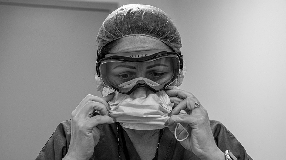 A black and white photo of a health care worker in goggles readjusts her face mask.