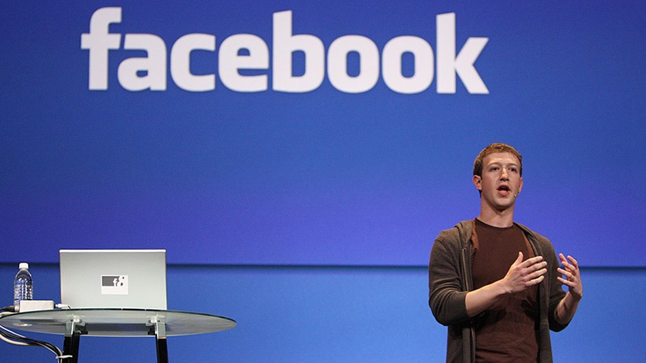 Mark Zuckerberg, in a brown t-shirt and hoodie, stands in front of a large blue backdrop with Facebook printed across the top. There is a high, round, glass-top table holding a laptop and water bottle across the stage from him.
