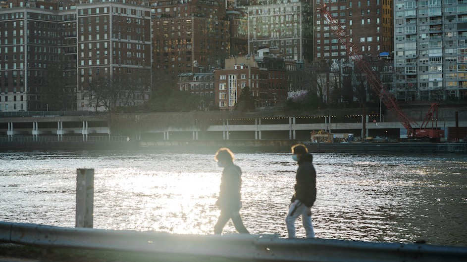 People with masks walking along the East River