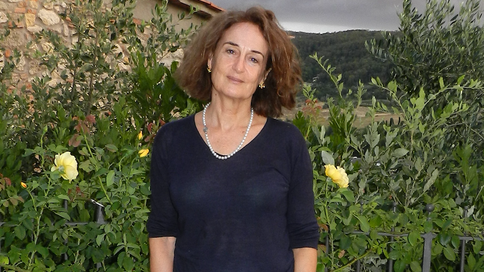 An image of a woman with shoulder length brown hair wearing a dark blue v-neck sweater standing in a garden