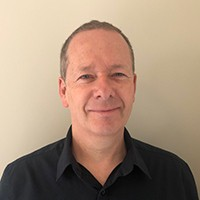 Headshot of a man with short hair in a dark shirt
