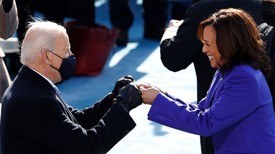 Joe Biden, in a black coat, double fist-bumps Kamala Harris, in a purple coat, on inauguration day 2021.