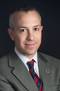 Headshot of a man with short hair in a grey suit, white shirt, and red and blue tie.