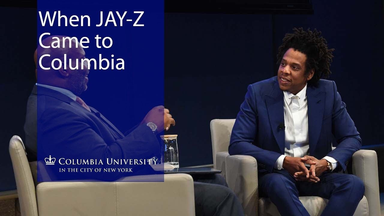 Jay-Z sits in a tan chair against a black backdrop.