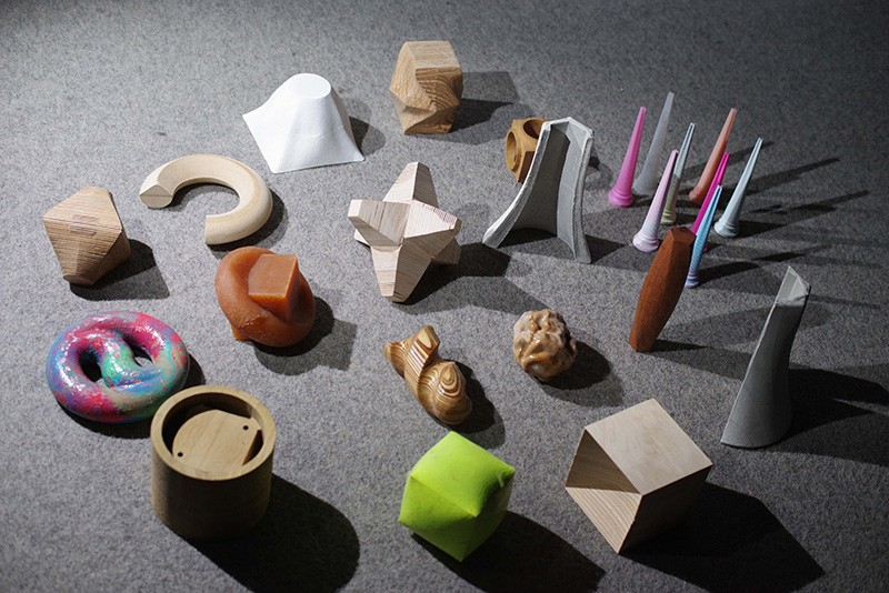 A collection of materials used in the Fabrication Lab--clay, plastic, wood, paper-- are arranged on a table.