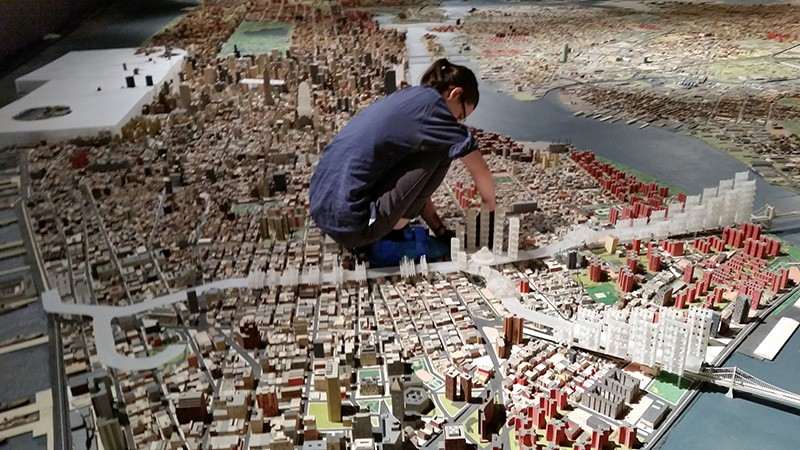 A woman stoops to work on a structurein the middle of a three-dimensional panoramic model of New York City.