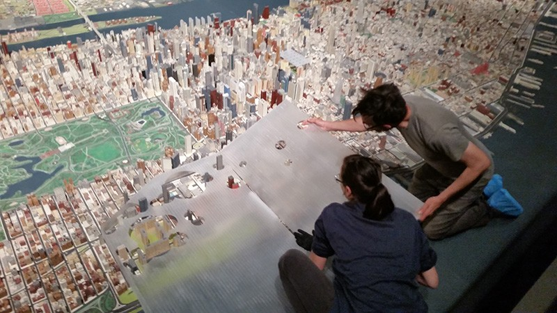 Two people lean over a three-dimensional model of Manhattan