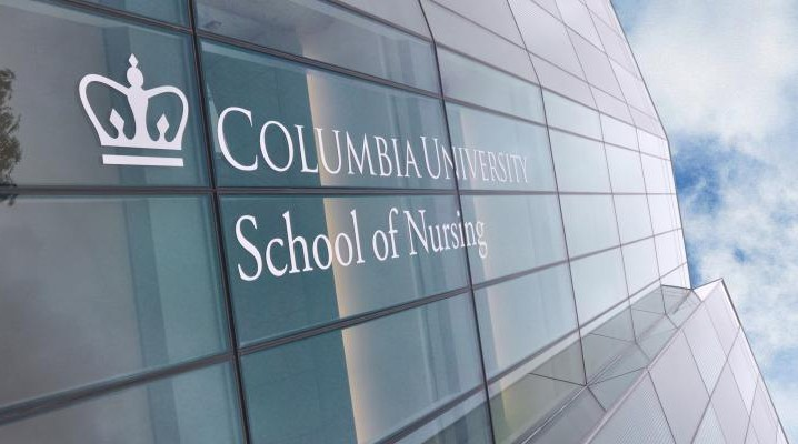 An image of the reflective facade of Columbia's School of Nursing, with the schools logo, featuring a stylized crown