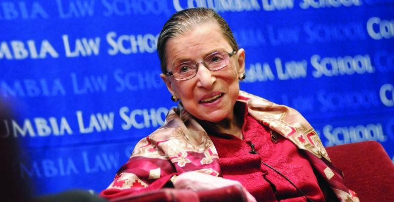 Ruth Bader Ginsburg in a red blouse in front of a blue Columbia Law School poster