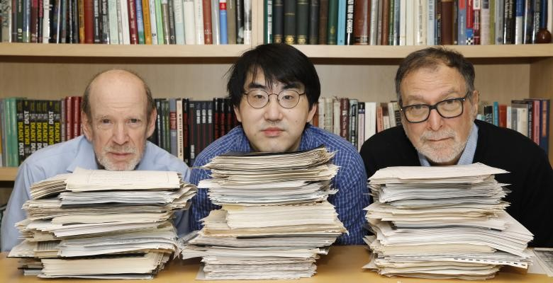 Three men rest their chins of stacks of documents piled on a desk