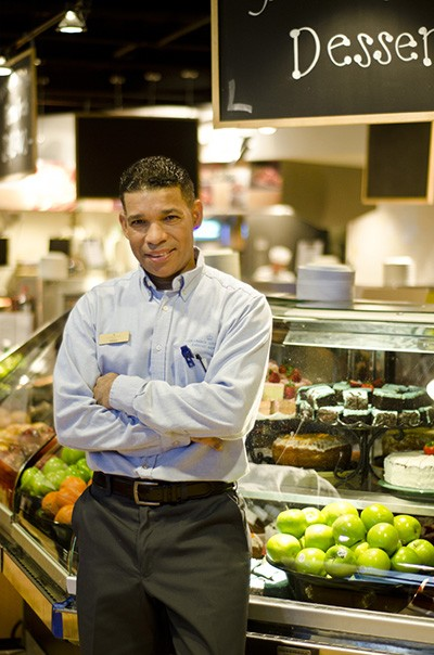 A man, smiling slightly and wearing a blue dress shirt and slacks, leans against a deli counter display filled with fresh fruit and pastry