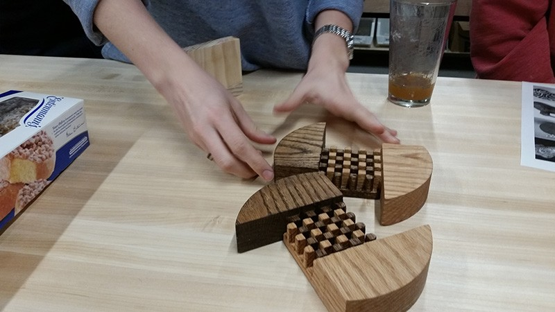 A pair of hands gesticulate toward two wooden boards with elaborate joinery on a table