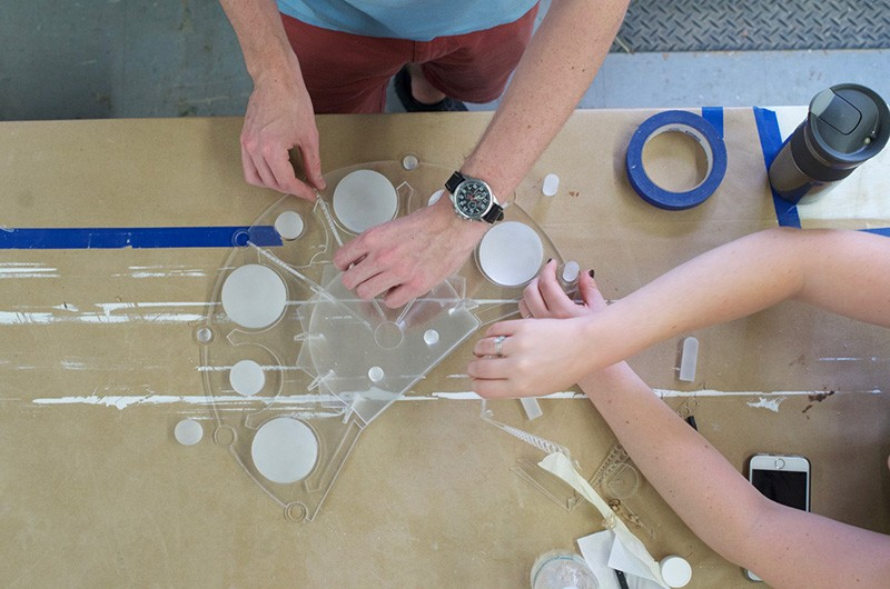 One person holds a clear,plastic mold in place while another fills cavities in the mold with a white liquid.