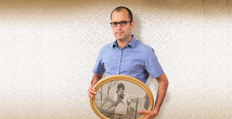 Yaniv Erlich holds a framed picture of his father as a teenager