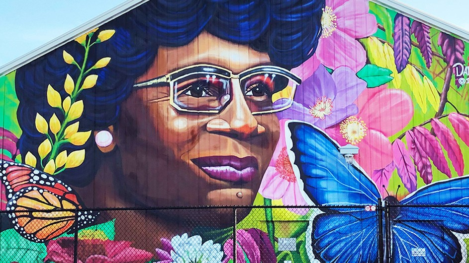 A colorful mural of Shirley Chisholm with flowers and butterflies around her face.