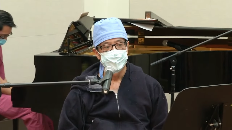 A surgeon with a bonnet and face mask sits at a microphone to sing and has a piano in the background.